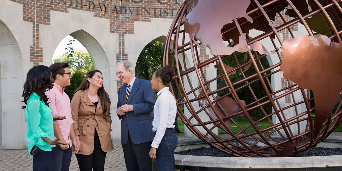 President Andreasen with students at the Andrews globe entrance